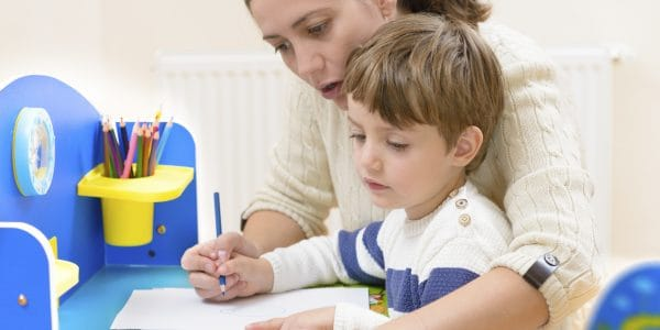 Mother helping son grip pencil correctly